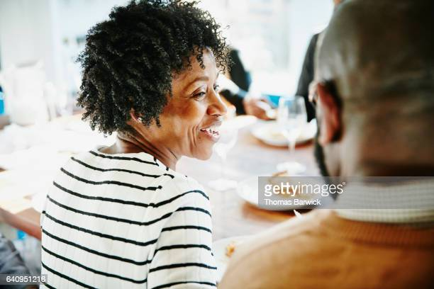 smiling woman in discussion with friend during holiday meal - african american christmas images stock pictures, royalty-free photos & images