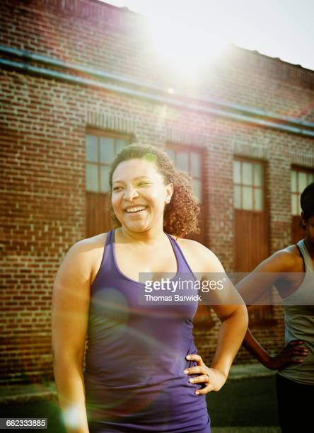 Smiling woman in discussion with friends after run