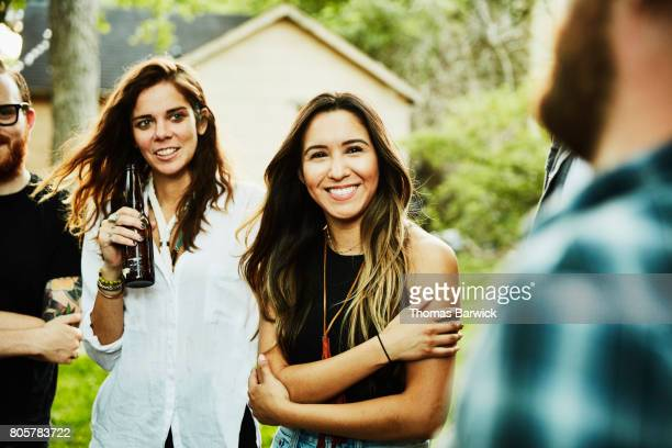Smiling woman in discussion with friends during backyard party