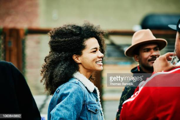 smiling woman in discussion with friends during party at outdoor bar - afro amerikaanse etniciteit stockfoto's en -beelden