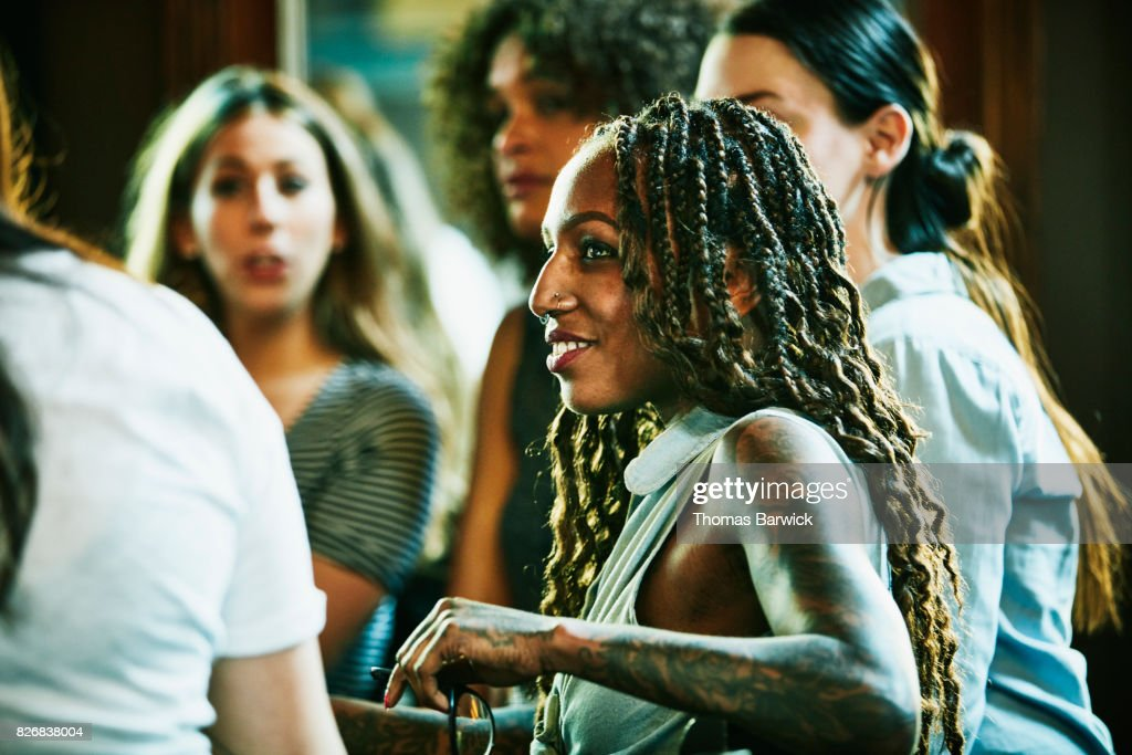 Smiling woman in discussion with friends in bar : Stock Photo