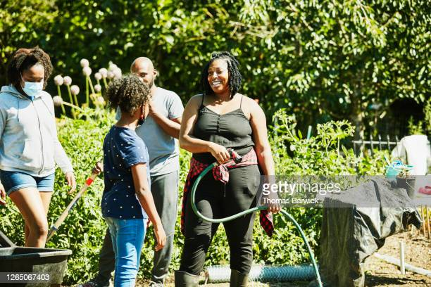 smiling woman in discussion with girl while volunteering with friends in community garden - environmentalist stock pictures, royalty-free photos & images