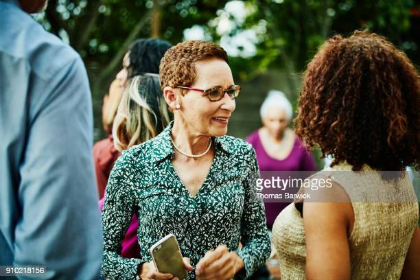 Smiling woman in discussion with sister inlaw after outdoor family dinner party