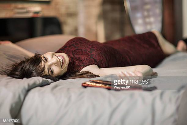 Smiling woman in evening dress on bed