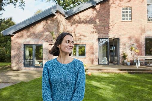 Smiling woman in garden of her home - gettyimageskorea