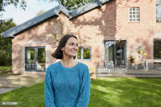 smiling woman in garden of her home - wohnhaus stock-fotos und bilder