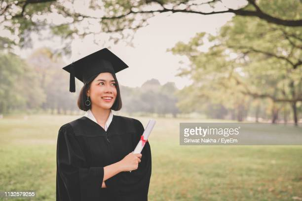 smiling woman in graduation gown standing on field at park - graduation clothing stock pictures, royalty-free photos & images