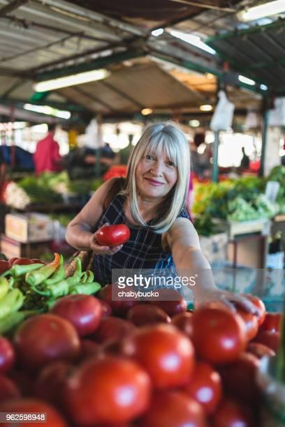 smiling woman in green market shopping vegetables - bancarella di verdura foto e immagini stock