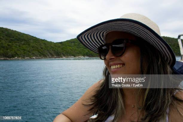 Smiling Woman In Hat And Sunglasses Against Sea