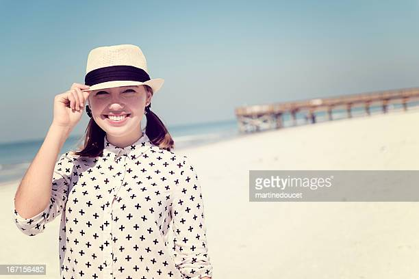 Smiling woman in hat on the beach in front of pier PPP