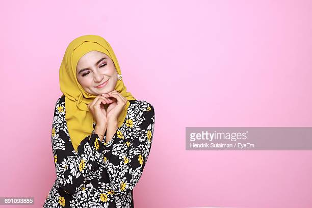 smiling woman in hijab standing against pink background - hijab - fotografias e filmes do acervo