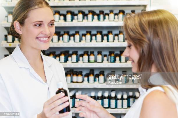 smiling woman in homeopathic pharmacy hands bottle to customer - homeopathic medicine stock photos and pictures