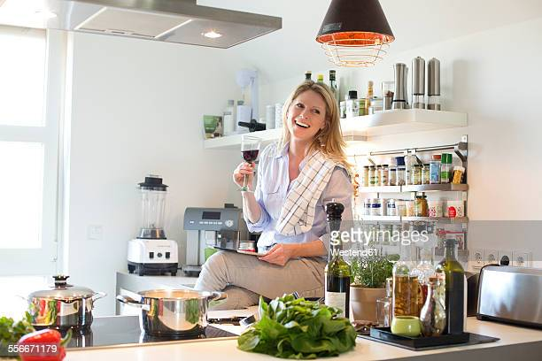 Smiling woman in kitchen drinking glass of red wine and using digital tablet
