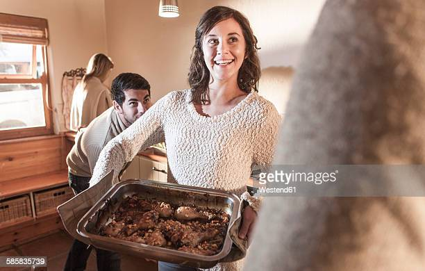 Smiling woman in kitchen serving meal