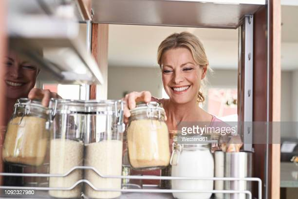 smiling woman in kitchen taking jar from kitchen cabinet - cuisine non professionnelle photos et images de collection