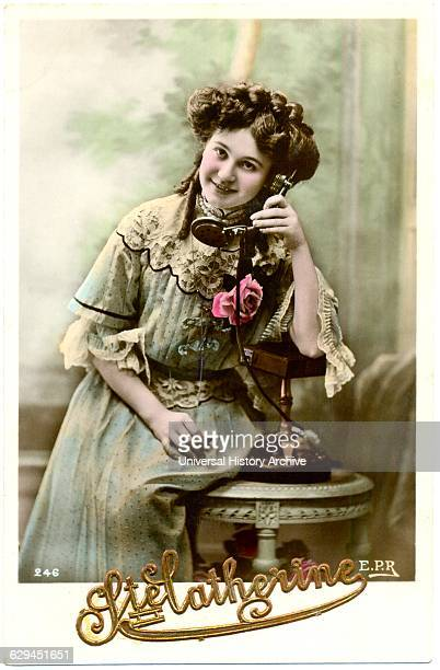 Smiling Woman in Light Blue Dress Sitting on Table Holding Telephone French Postcard circa 1911