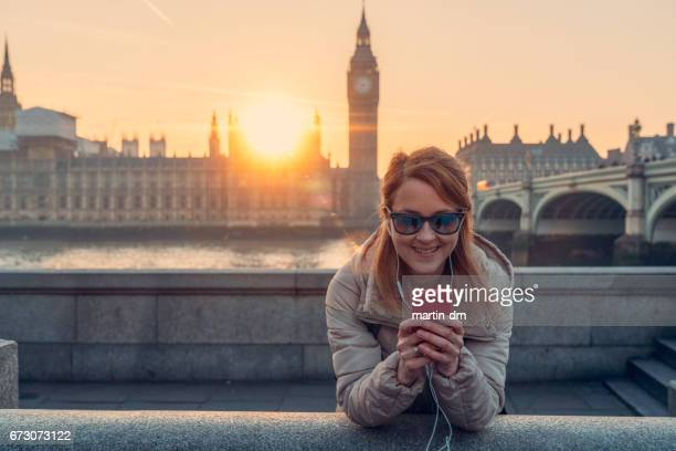 Smiling woman in London texting