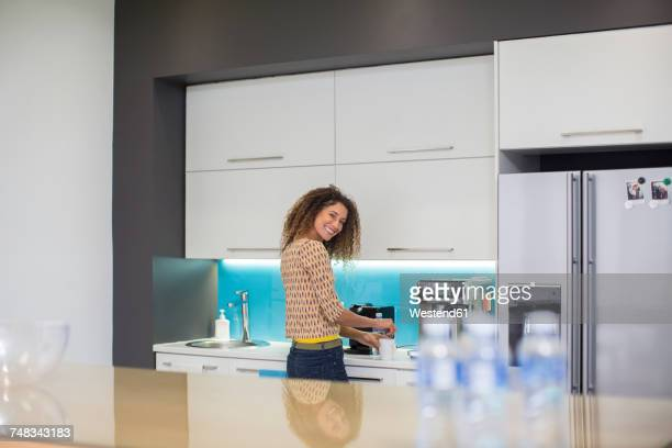 Smiling woman in office kitchen making a beverage