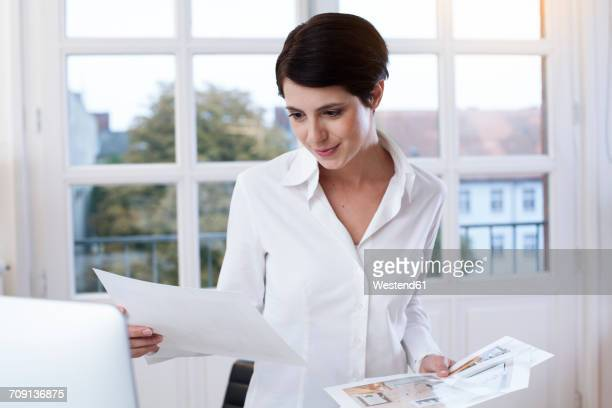 Smiling woman in office looking at papers