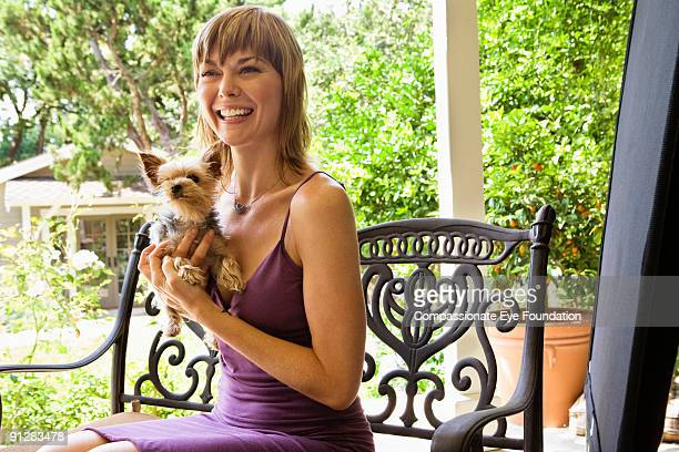 Smiling woman in purple dress holding small dog