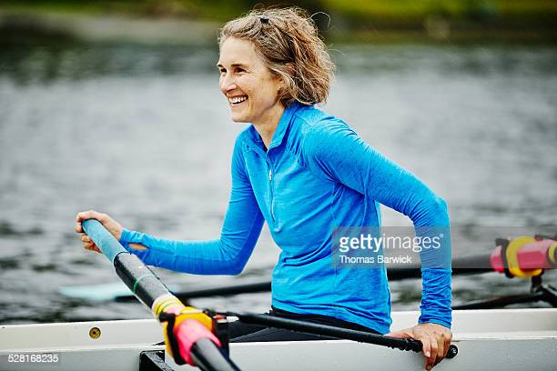 Smiling woman in rowing shell during practice