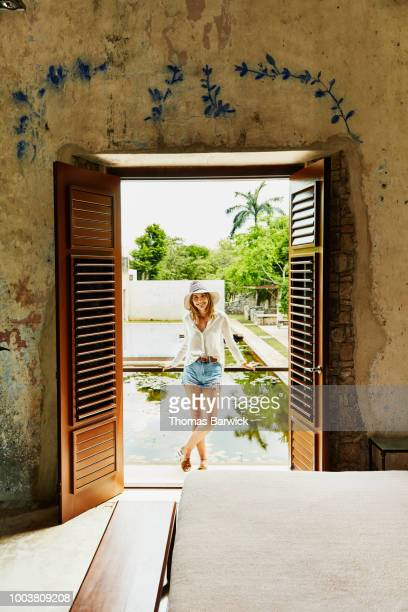 Smiling woman in sun hat standing on balcony of room at tropical luxury resort