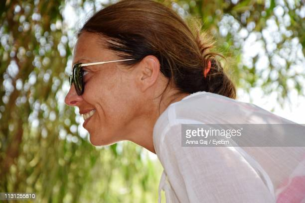 Smiling Woman In Sunglasses By Tree