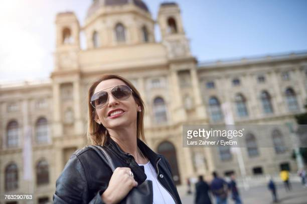 Smiling Woman In Sunglasses Standing Against Kunsthistorisches Museum