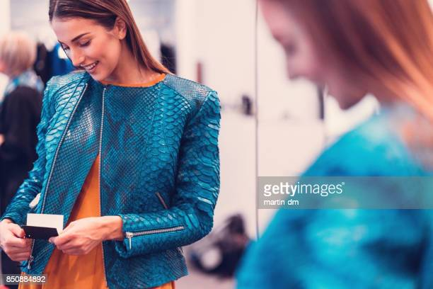 smiling woman in the boutique measuring a leather jacket - jacket stock pictures, royalty-free photos & images