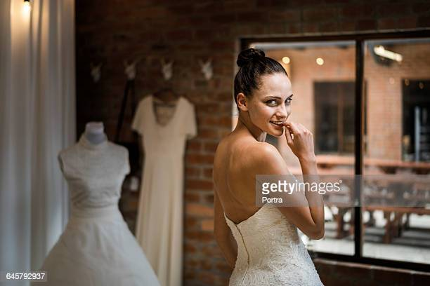 Smiling woman in wedding dress is biting nail