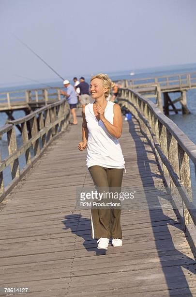 Smiling woman jogging along boardwalk