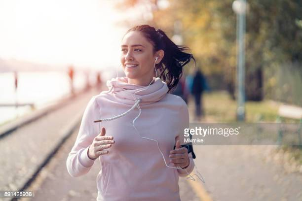 smiling woman jogging and listening to music - jogging stock photos and pictures