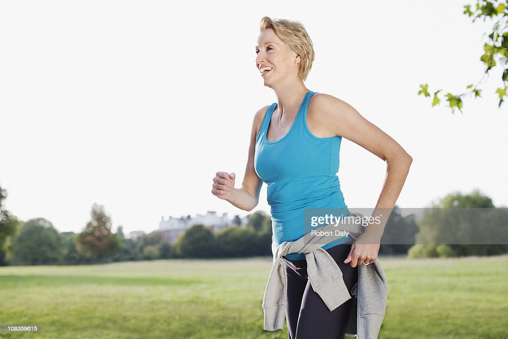 Smiling woman jogging in park : Stock Photo