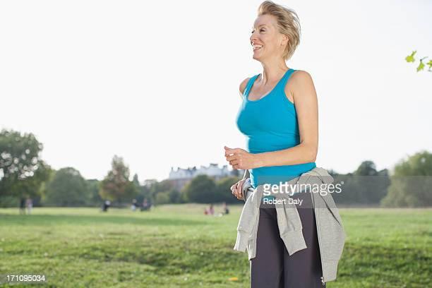 笑顔の女性の公園でジョギング