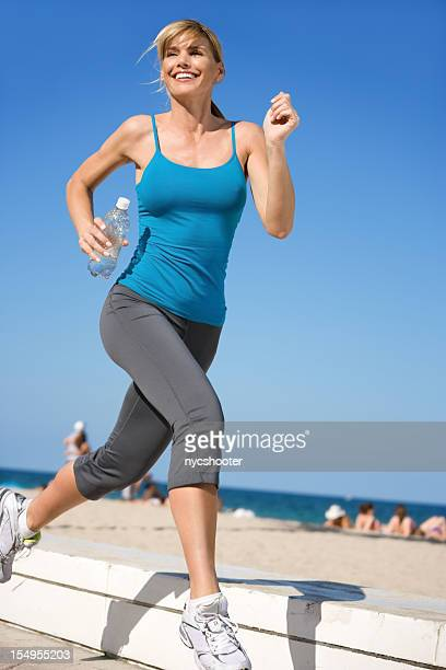 A smiling woman jogging in workout clothes
