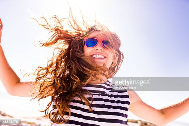 Smiling woman jumping on sunny day