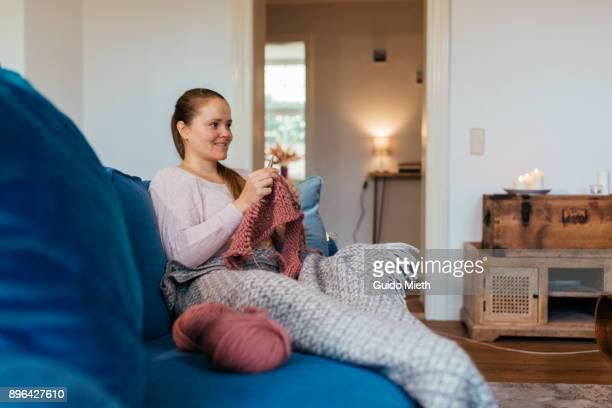 smiling woman knitting at home. - tricoté photos et images de collection