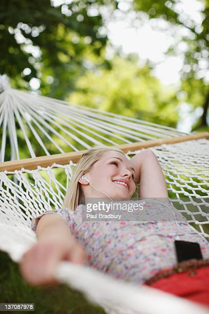 Smiling woman laying in hammock and listening to music on mp3 player and headphones