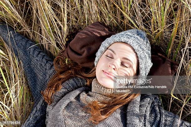 Smiling woman laying in wheatfield