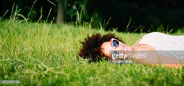 Smiling woman laying on green grass