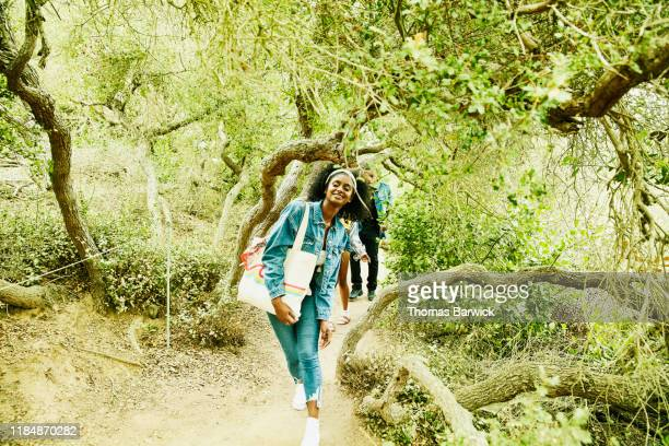 Smiling woman leading friends through tunnel of trees while exploring park