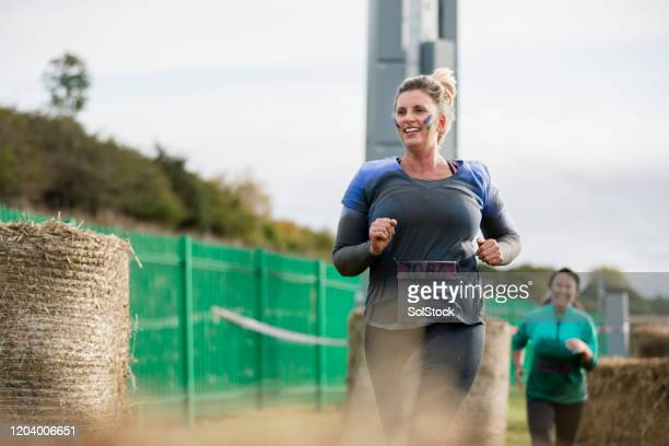 smiling woman leading outdoor charity run - running stock pictures, royalty-free photos & images
