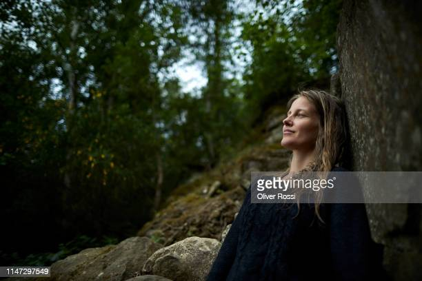 smiling woman leaning against a rock in nature - lehnend stock-fotos und bilder