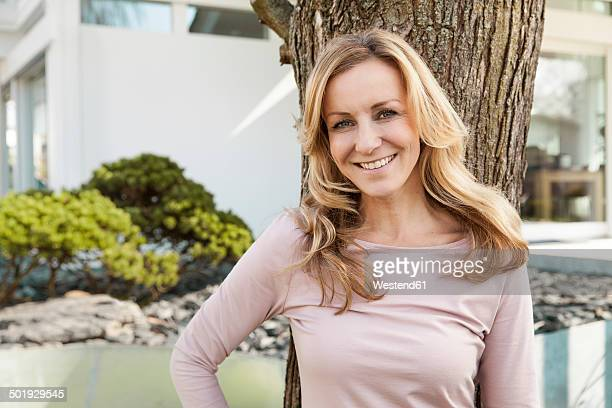 smiling woman leaning against a tree in front of residential house - one mature woman only stock pictures, royalty-free photos & images