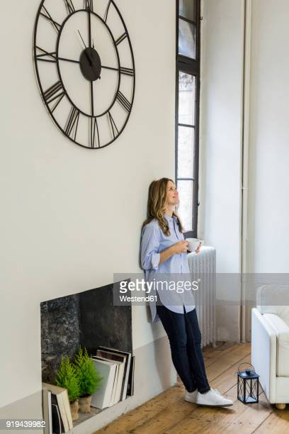 smiling woman leaning against the wall under clock at home - もたれる ストックフォトと画像