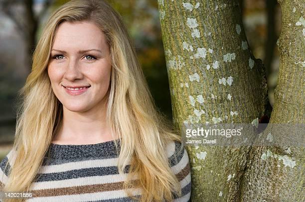 Lächelnde Frau schiefen gegen Baum