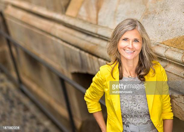 Smiling Woman Leaning Against Wall