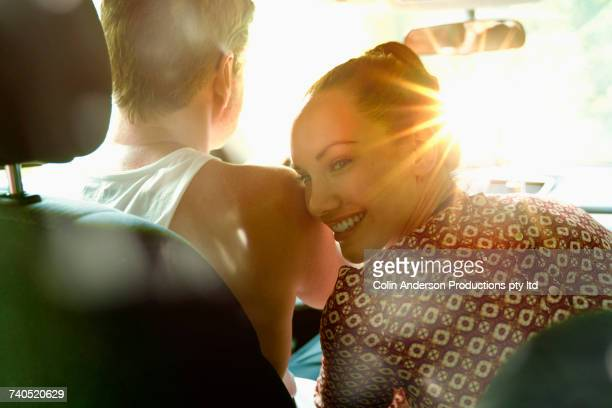 Smiling woman leaning head on shoulder of man driving sunny car