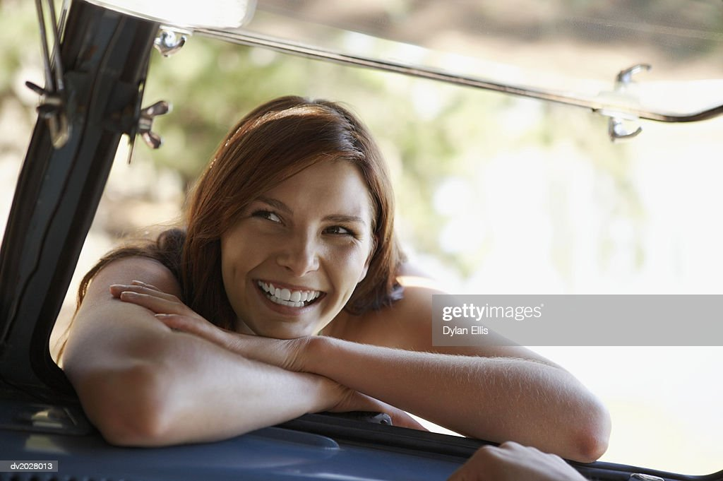 Smiling Woman Leaning in a Car Window : Stock Photo