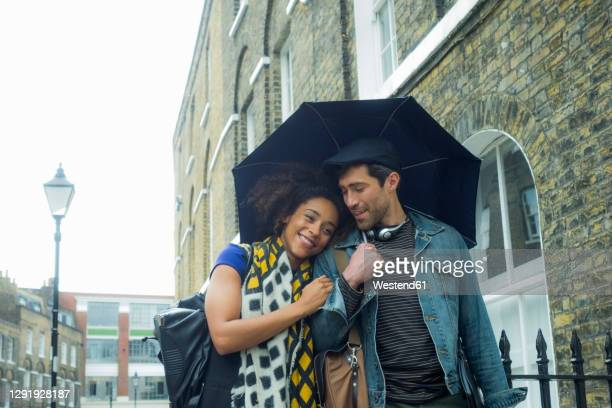 smiling woman leaning on man holding umbrella while walking at city - 30 39 years stock pictures, royalty-free photos & images